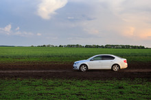 A White Car On The Road, In The Background A Green Field.