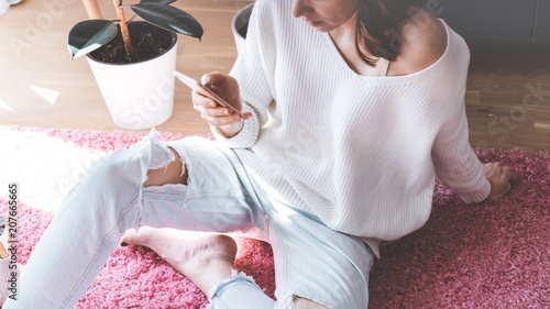 Fotografia, Obraz  Handsome girl sitting on pink carpet on the floor at modern light coloured livin