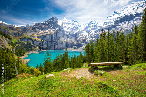 Fotobehang Weg in bos Amazing tourquise Oeschinnensee lake with waterfalls, wooden chalet and Swiss Alps, Berner Oberland, Switzerland