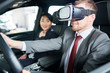 Joyful bearded man wearing elegant suit wrapped up in virtual test-drive of new car model with help of VR headset while pretty saleswoman looking at him with wide smile.