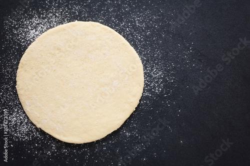 Rolled out pizza dough on floured slate surface, photographed overhead with natu Fototapeta