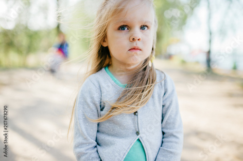 Little adorable beautiful child closeup portrait. Young small girl with long hair and emotional expressive face mood outdoor summer portrait. Different facial expressions. Childhood. Baby on road.