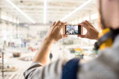 Fotografía  Over shoulder view of unrecognizable inspector wearing ear protectors standing at spacious production department of modern plant and taking picture on smartphone while carrying out inspection