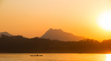 Boat Fisherman Silhouette At Sunset On Mekong River