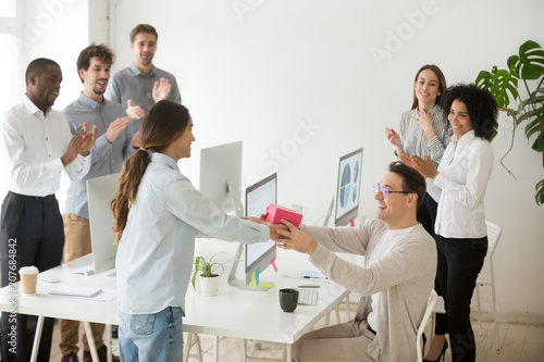 Fototapeta  Smiling female employee congratulating colleague with birthday, presenting gift