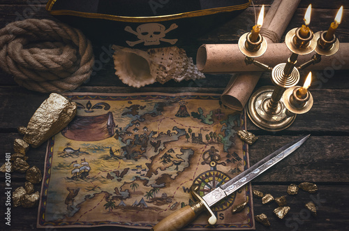 Fotografija Pirate treasure map, gold nuggets, dagger and pirate hat on aged wooden table background