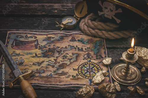 Pirate treasure map, gold nuggets, dagger and pirate hat on aged wooden table background Canvas Print