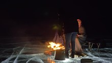 Three Travelers By Fire Right On Ice At Night. Campground On Ice. Tent Stands Next To Fire. Lake Baikal. Nearby There Is Car. People Are Warming Around Campfire And Are Dressed In Sleeping Bags. This