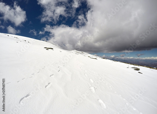 Fotobehang Wit Trail on an icy hillside on a blue day