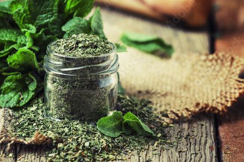 Wysuszona miętówka w szklanym słoju i wiązce świeża mennica, rocznika drewniany tło, selekcyjna ostrość