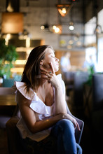 Relaxed Young Woman Sitting At Cafe And Wearing Silver Ring With Emerald Ethnic Jeans. Concept Of Fashion And Beauty.