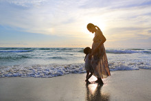 Pregnant Mother And Daughter Relaxing On The Beach At Sunset.