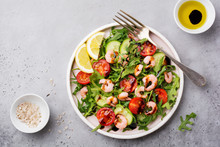 Arugula, Cucumber, Tomato And Shrimp Salad With Soy Sauce On A Ceramic Plate. Selective Focus. Top View.
