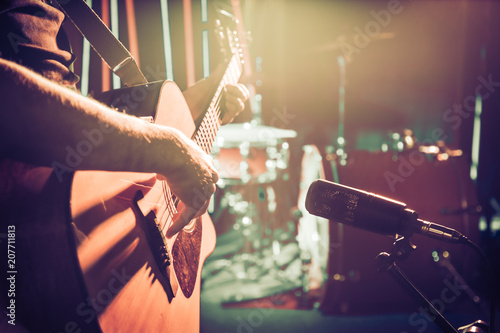 Obraz The Studio microphone records an acoustic guitar close-up. Beautiful blurred background of colored lanterns. - fototapety do salonu