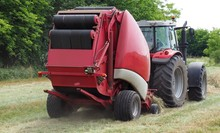 Hay Baler Machine Pulled By A Red Tractor On A Freshly Cut Field