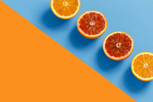 Oranges Cut In Half On A Orange And Blue Background