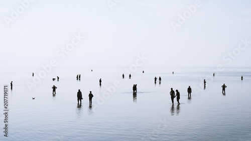 Fotografia large group of people or crowd standing walking and swimming in shallow water at