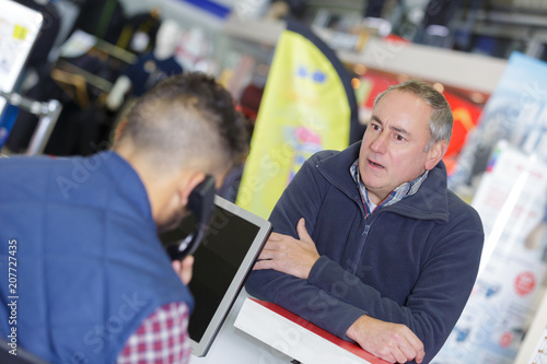Fotografie, Obraz  man getting impatient while shop keeper is on telephone