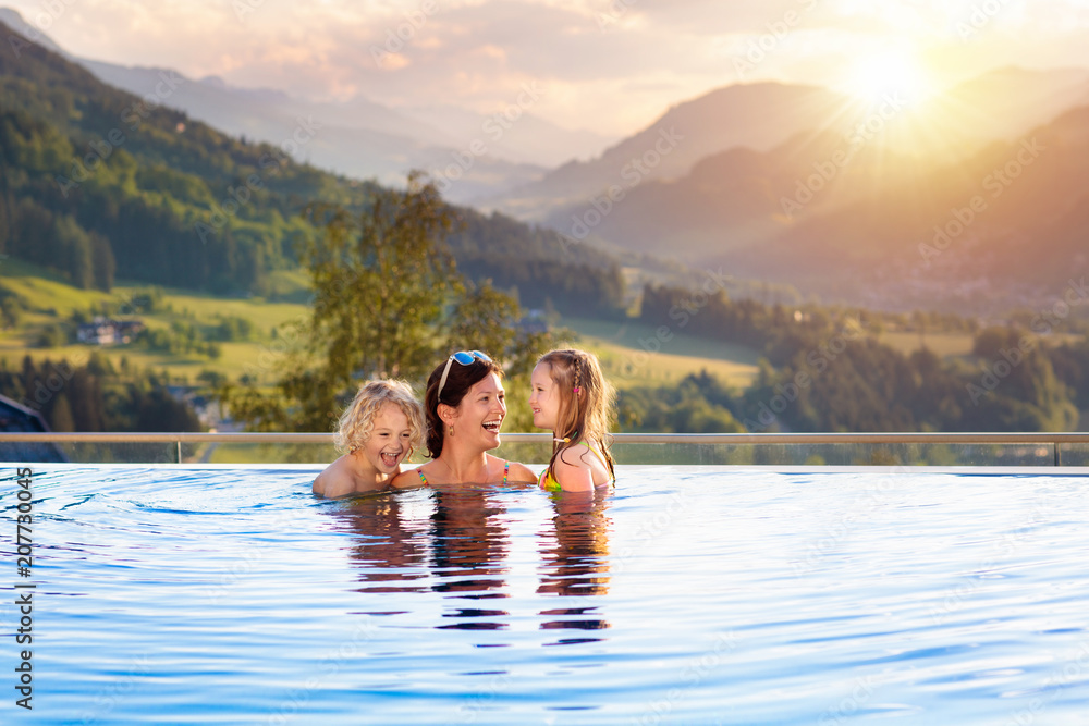 Fototapeta Family in swimming pool with mountain view