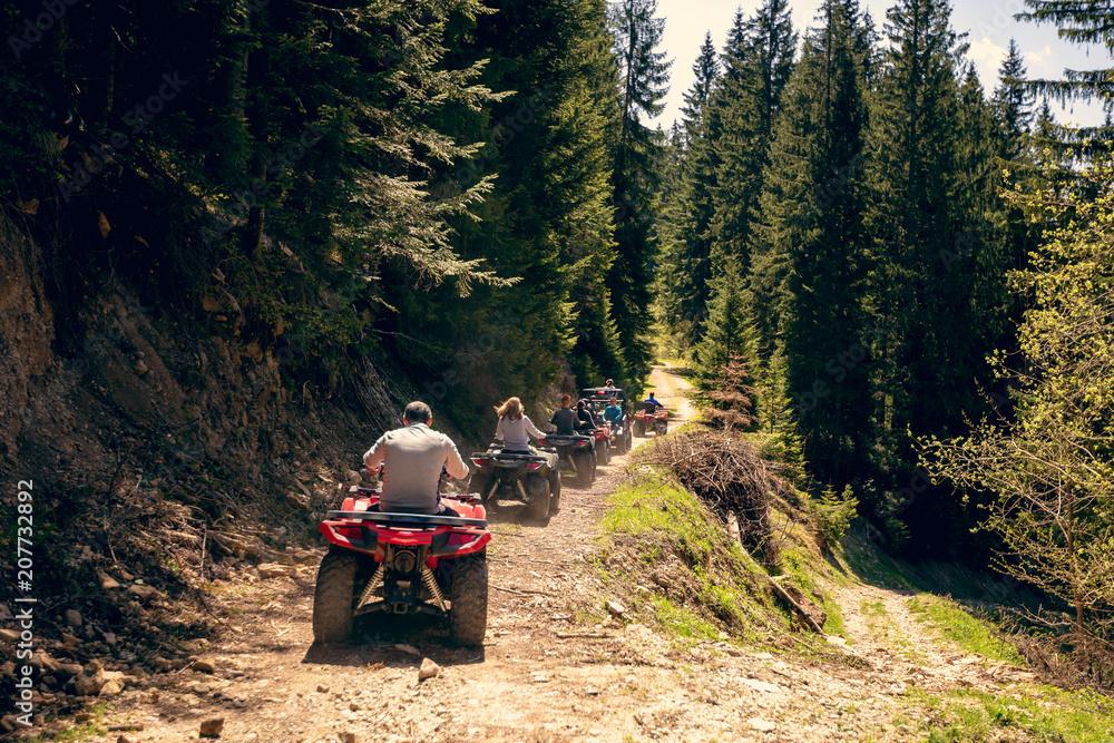 Fototapeta A tour group travels on ATVs and UTVs on the mountains