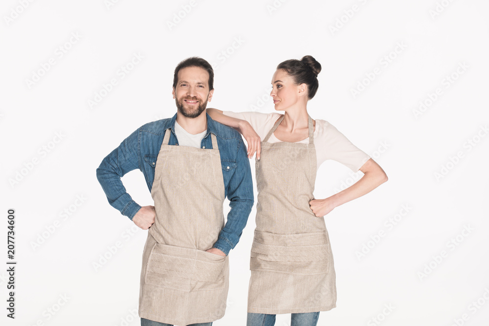 Fototapeta portrait of man and woman in aprons isolated on white