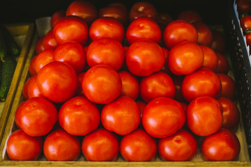Beautiful and fresh red tomatoes on a shelf in a supermarket. Seasonal and exotic vegetables and fruits
