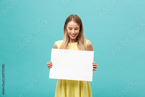 Beautiful woman holding a blank billboard isolated on blue background