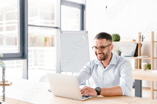 Fotomural Photo of joyous office man 30s in white shirt sitting at desk and working on lap