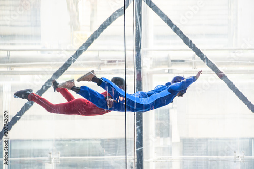 Valokuva  Skydivers in indoor wind tunnel, free fall simulator