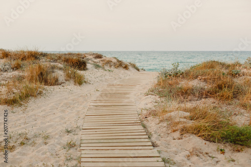 Photo Payment Management Wooden path over the sand of the beach dunes