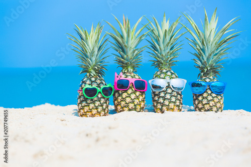 Tropical vacation travel concept, fresh pineapple on tropical white sand beach with sunglasses, Summer travel