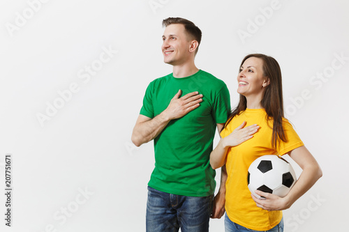 Emotional couple, woman man, football fans in yellow green t-shirt cheer up support team with soccer ball singing national country anthem isolated on white background Wallpaper Mural