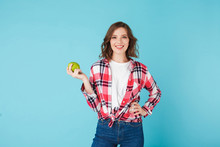 Smiling Beautiful Lady In Plaid Shirt And Jeans Holding Green Apple While Happily Looking In Camera Over Blue Background Isolated