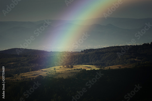 rainbow landscape, summer evening with rainbow over hills