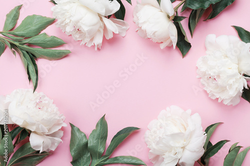 Floral frame of white peony flowers on pink pastel table top view and flat lay style. Fashion summer color.