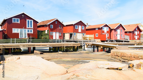 Photo Red wooden boathouses on a sunny day in Smogen on the Swedish west coast