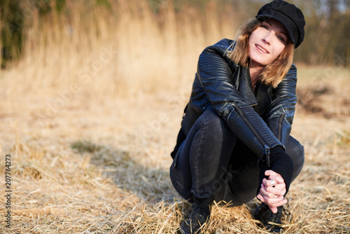 Cool woman wearing cap crouching on field straw, portrait