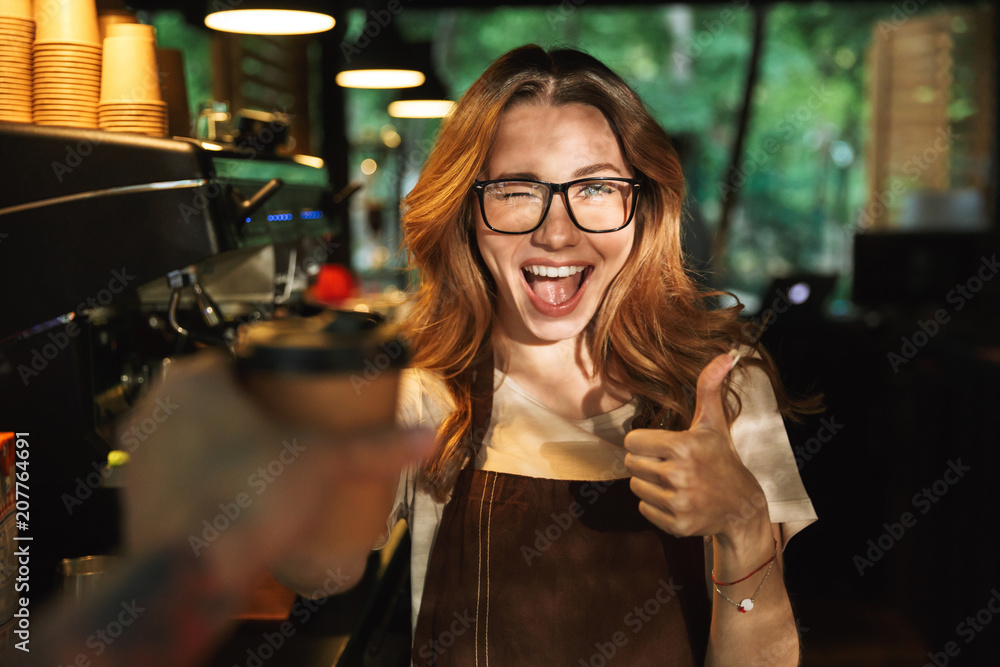 Fototapeta Portrait of a happy young barista girl in apron