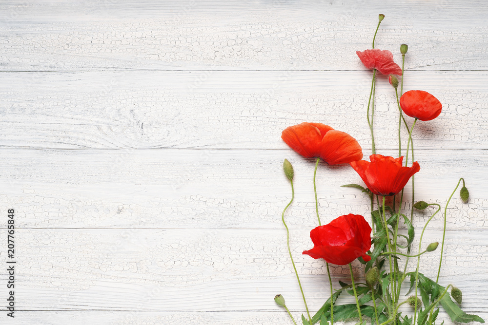Red poppy flowers on white rustic wooden surface.