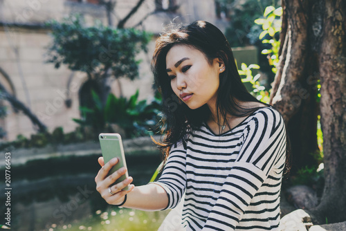 Beautiful model look asian hipster girl with long dark hair in a striped longsleeve t-shirt is taking selfie by a camera of the mobile phone while sitting on a natural plants background on a sunny day