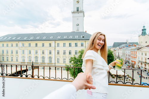 Fotografía  happy sensual young woman with lemonade glasses holding someone hand, looks at camera enjoying the european city view