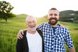 canvas print picture A portrait of an adult hipster son with senior father in nature at sunset, arms around each other.