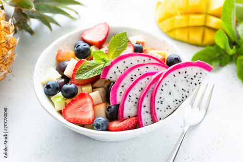 Thai fruit salad with pitaya and mango in a white bowl, closeup view. Concept of summer, holidays, vegetarian and vegan diet, healthy eating and healthy lifestyle