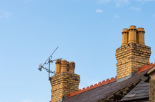 Old Residential Rooftop And Chimneys With TV Ariel. Slate Roof, Decorative Red Terracotta Ridge Tiles, Yellow Brick Chimney Stacks And Chimney Pots. Blue Sky Background With Copy Space.