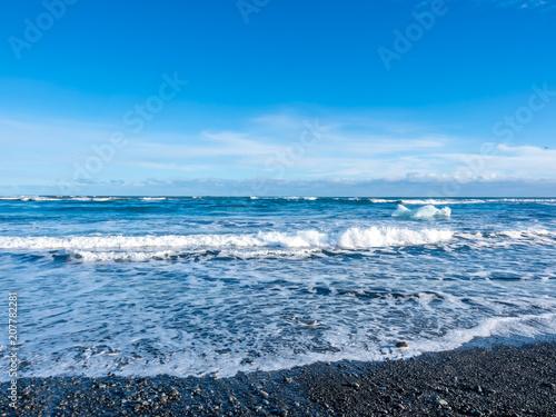 Poster Scandinavië Large ice at black sand beach in Iceland
