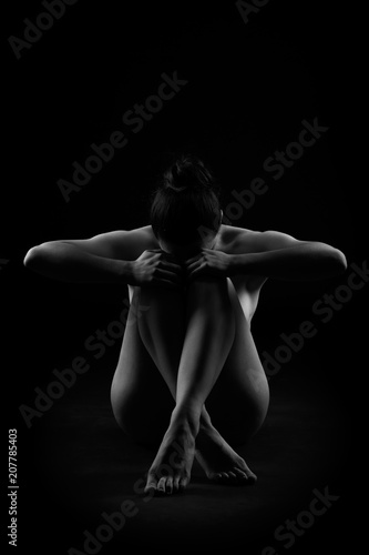 Art nude, perfect naked body, sexy woman sitting on dark background, black and white studio shot