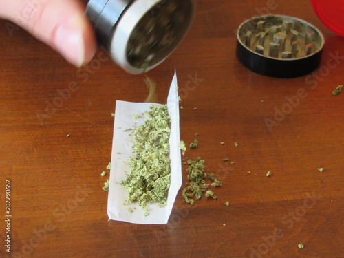 Photo  Man using grinder to fill rolling paper with prescription medicinal marijuana, t