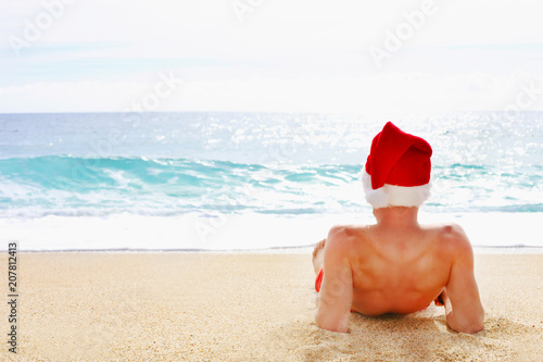 Christmas In July Swimsuit.Rear View Of Fit Young Man In A Santa Hat Celebrating