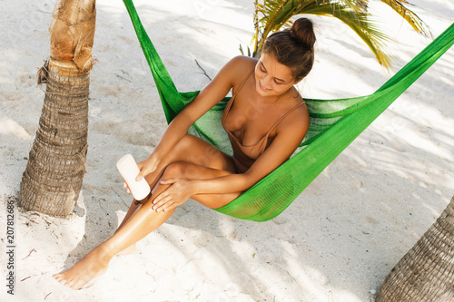 Beautiful woman in the hammock is applying sunscreen lotion.