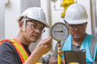 Two Asian engineer working in the boiler room,maintenance checking technical data of heating system equipment,Thailand people,Discuss the issue about the pipe pressure.
